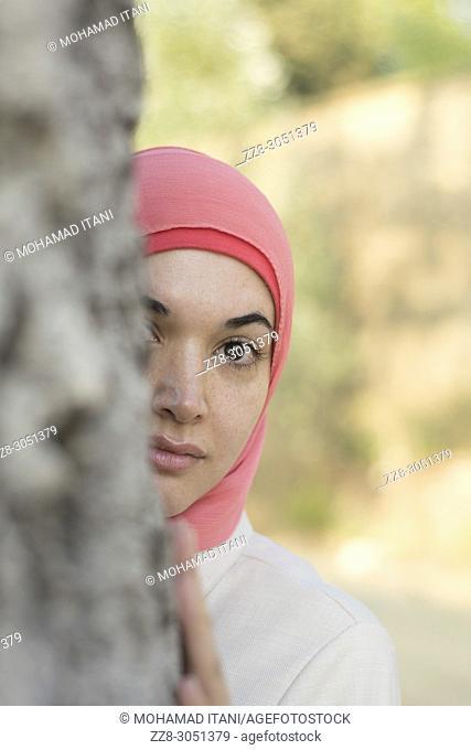 Muslim woman hiding behind a tree