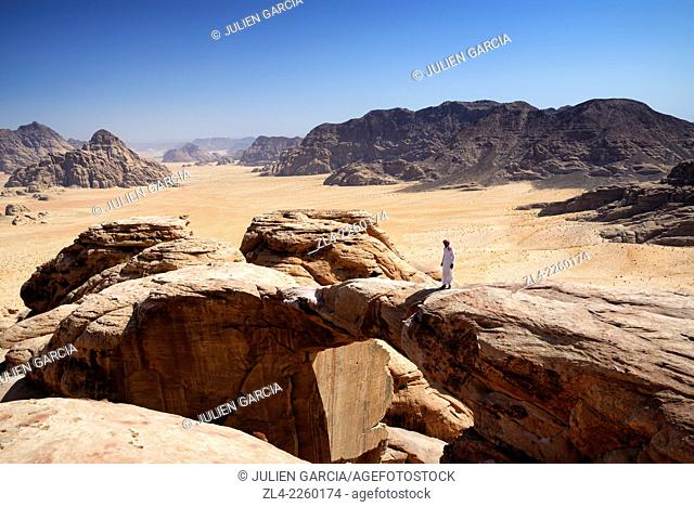 Bedouin on a natural rock arch, Burdah rock bridge, at the top of mount Jebel Burdah. Jordan, Wadi Rum desert, protected area inscribed on UNESCO World Heritage...