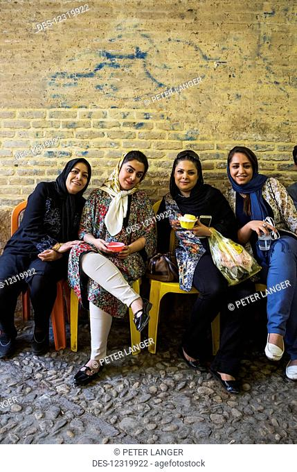 Young women enjoying fallodeh frozen dessert at the Vakil Bazaar; Shiraz, Fars Province, Iran