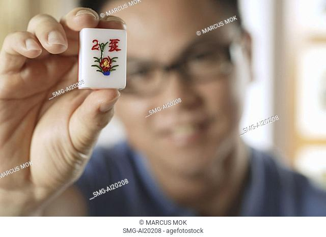 Man holding mahjong tile with the Chinese script for Summer