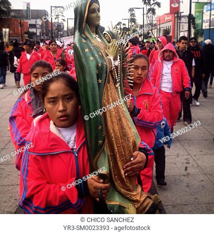 A woman holds an image of the Virgin of Guadalupe during the annual pilgrimage to the Our Lady of Guadalupe basilica in Mexico City, Mexico