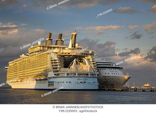 Royal Caribbean's gigantic Oasis of the Seas Cruise ship dwarfs a more 'normal' sized ship in port, Cozumel, Yucatan, Mexico
