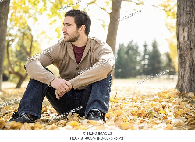 Thoughtful young man sitting on fallen leaves in park