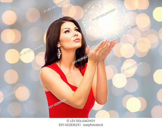 people, holidays, christmas, magic and fashion concept - beautiful sexy woman in red dress blowing fairy dust off over lights background