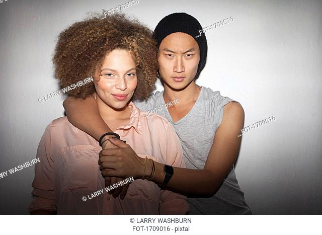 Portrait of young couple standing against white wall