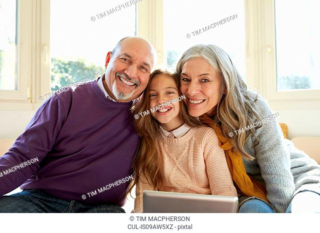 Grandparents on window with granddaughter holding digital tablet looking at camera smiling
