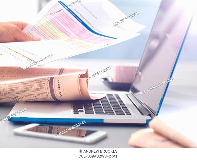 Man reviewing financial affairs using newspaper market data, investment statement and laptop