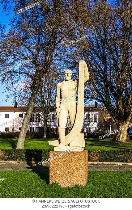 Sculpture 'De Scheepstimmerman' on the Enkhuizerplein in 1960 by Johan Polet looking at the village of Nieuwendam, where many ships used to be built