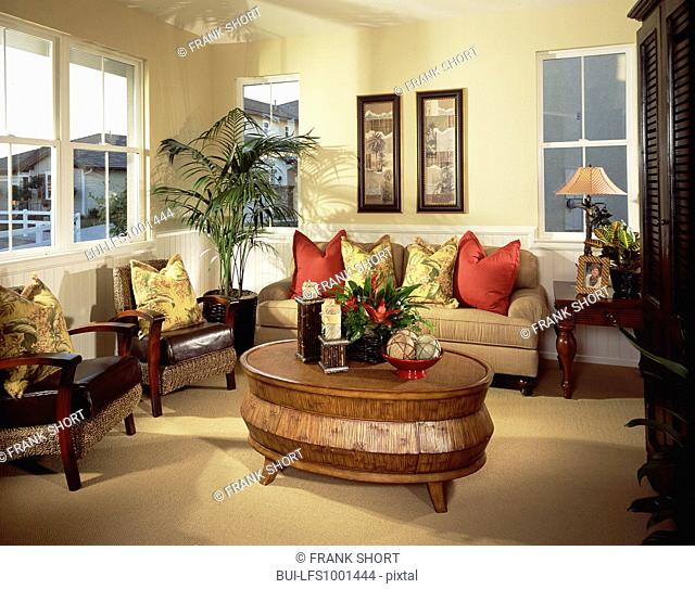Red and yellow cushions on seating furniture by coffee table
