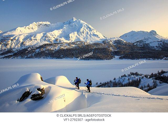 Snowshoe hikers reach a lookout on the Piz de la Margna. Maloja Pass. Engadine. Switzerland. Europe