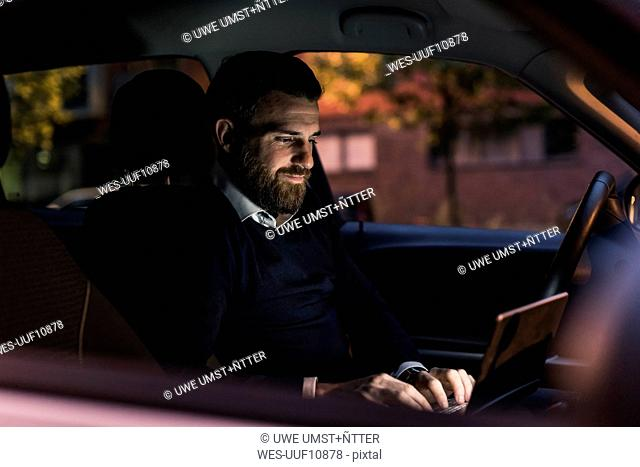 Businessman using laptop in car at night