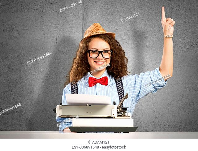 Young pretty woman writer with typing machine