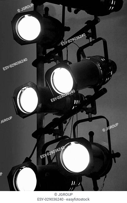 Stage lights on a vertical rig in black and white