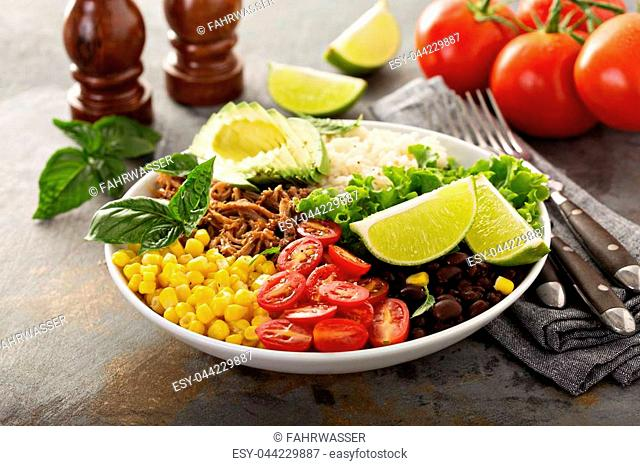 Mexican salad bowl with rice, pulled pork, corn, black beans and avocado