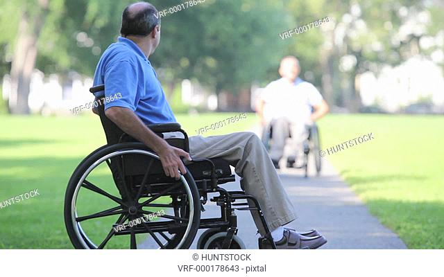 Two men in wheelchairs in a park greeting each other one with spinal cord injury and one with Friedreich's Ataxia