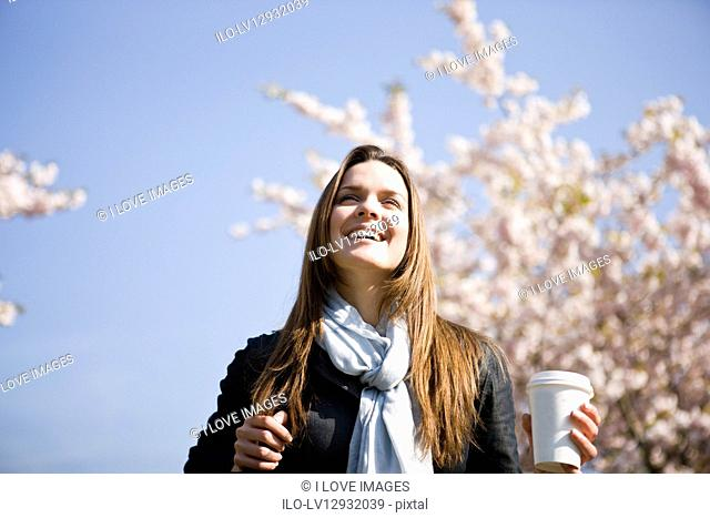 Portrait of a young woman holding a hot drink, in springtime