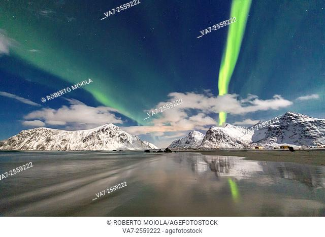 Northern Lights and mountains reflected in the cold waters. Skagsanden. Lofoten Islands Northern Norway Europe