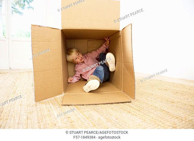 Four year old boy playing in a cardboard box