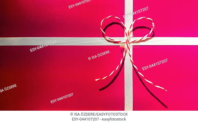 Front view of pink and red color decorated gift box with ribbons and Christmas decor