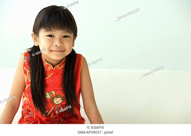 Girl in traditional clothes smiling at camera