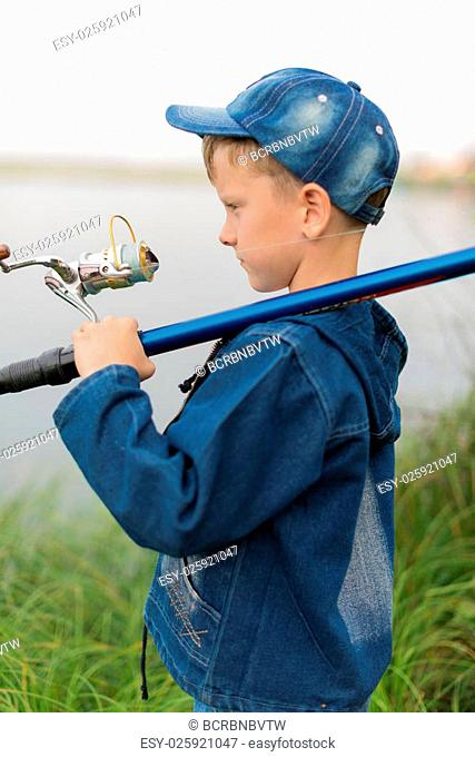 Attentive , focused, serious child is on a summer fishing on the river with a fishing rod in his hands