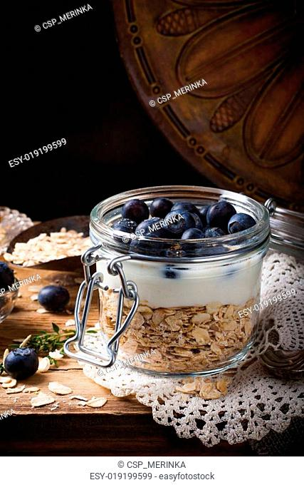 Muesli with yogurt and blue berries in glass jar