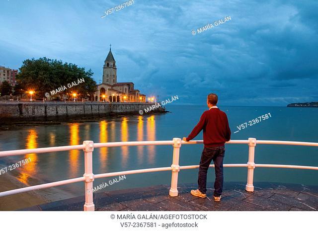 Man on the promenade, night view. Gijon, Asturias, Spain
