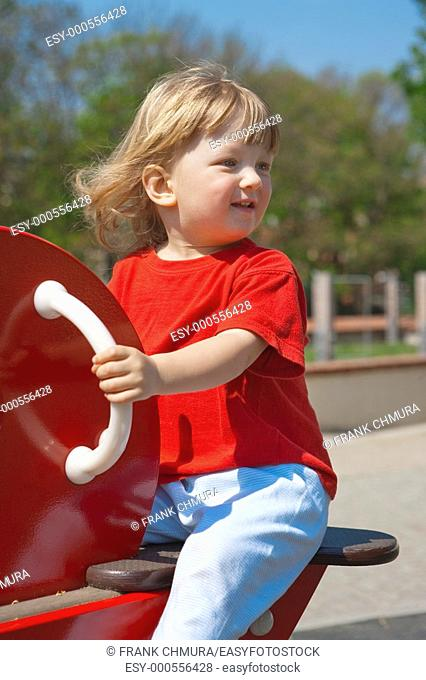 happy boy with long blond hair swinging at the playground