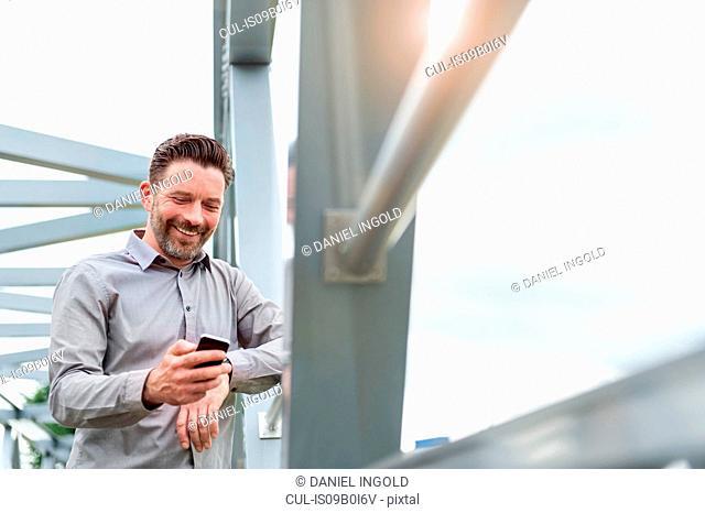 Mature businessman reading smartphone texts on footbridge