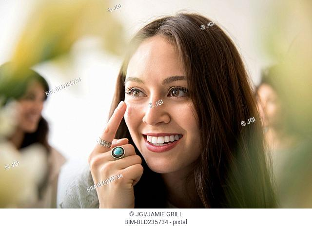 Smiling woman applying moisturizer to face