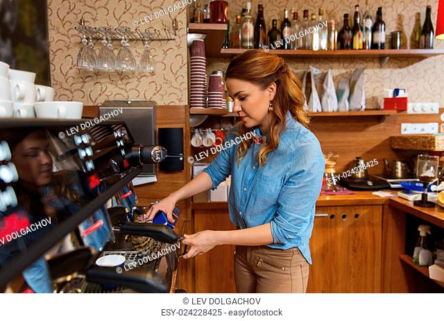 equipment, coffee shop, people and technology concept - barista woman pouring cream to jug at coffee machine