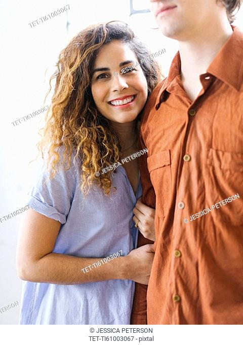 Couple standing against window
