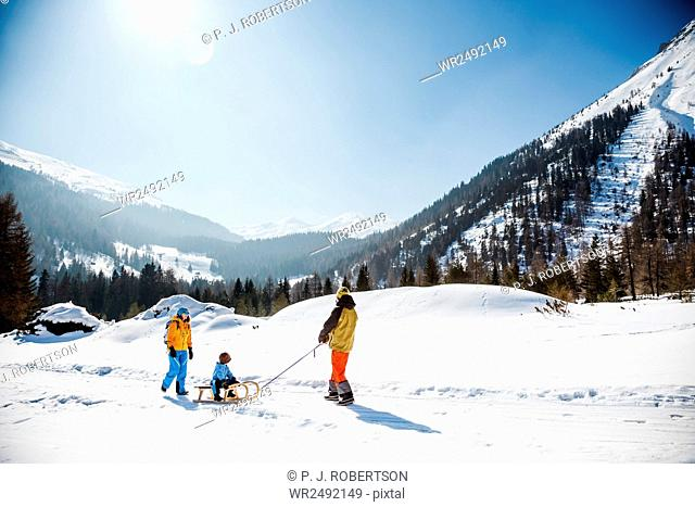 Family pulling sledge with son in Alpine scenery