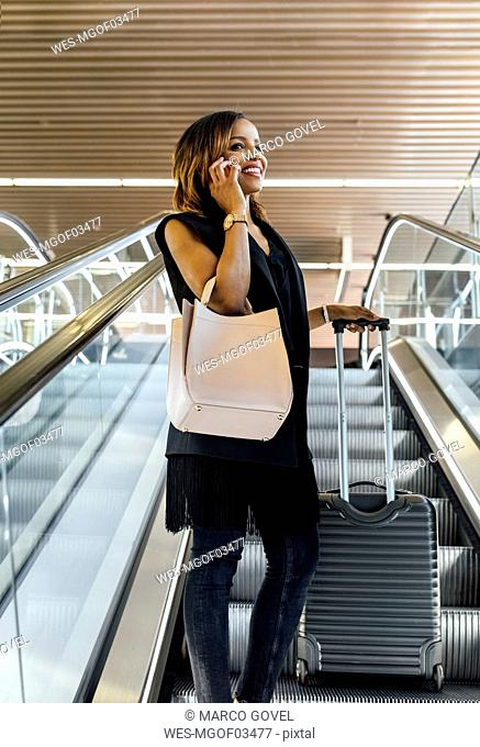 Smiling woman talking on the phone on escalator