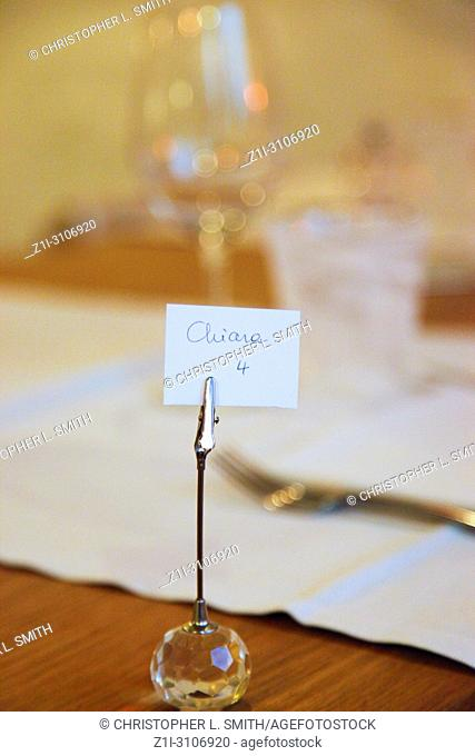 Reservation card at a table at Trattoria Antica Maddalena restaurant on Via Pelliccerie in Udine, Italy