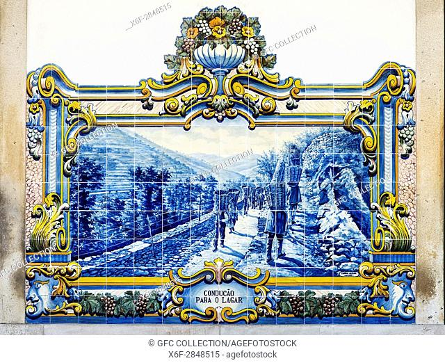Historic ceramic tile (azulejos) displaying a panoramic scene of the wine harvest in the Douro region, train station of Pinhao, the tile panel were painted by J