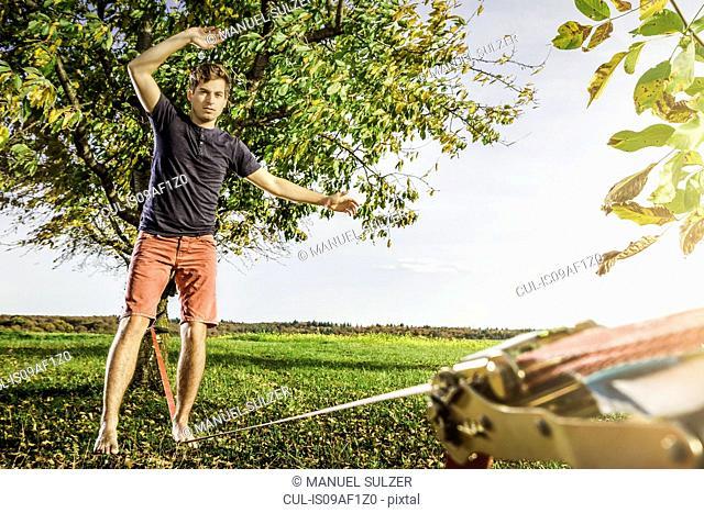 Portrait of young man balanced on slackline
