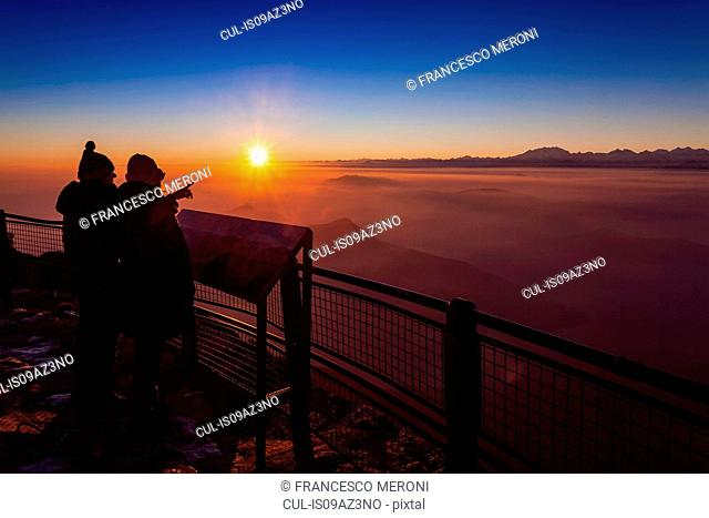 Senior hiking couple looking out over mountain valley mist at sunset, Monte Generoso,Ticino, Switzerland