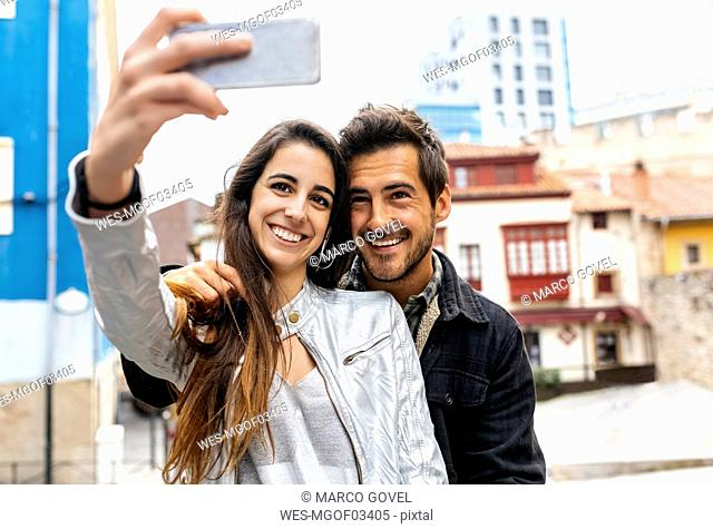 Smiling couple taking a selfie in the city