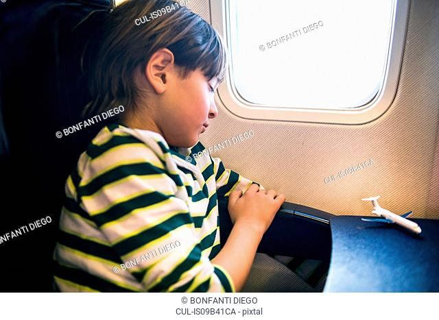 Boy on airplane asleep in airplane window seat