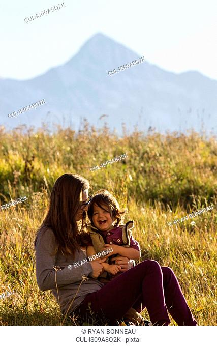 Mother sitting holding toddler in long grass