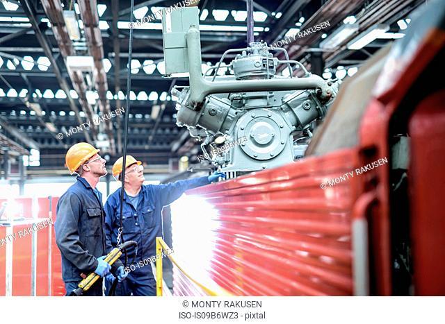 Locomotive engineers craning engine parts in train works