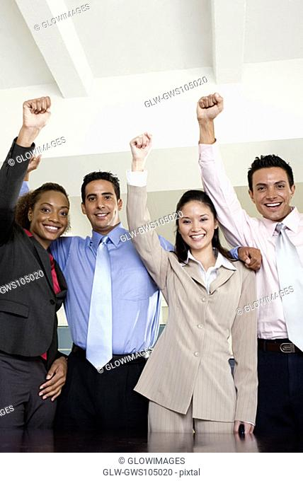 Portrait of two businessmen and two businesswomen standing with their hands raised