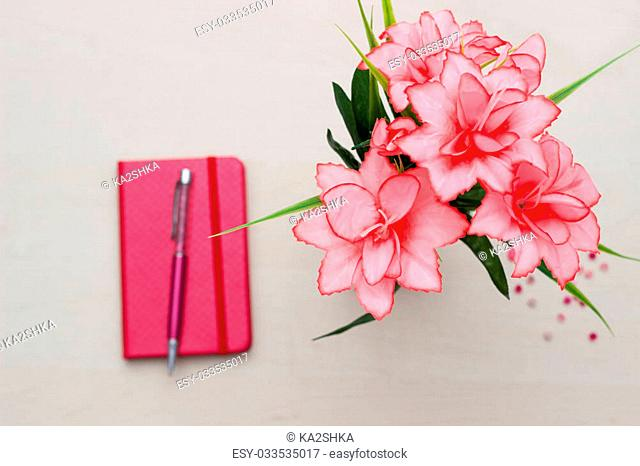 Notebook with flower on wooden background