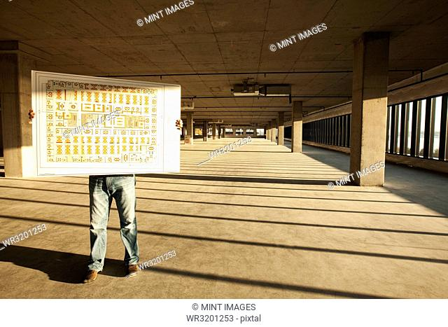 Businessman holding up plans for new office space standing in the middle of the empty raw space