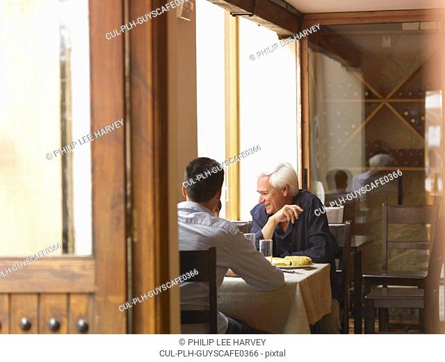 Boy 8-10 sitting at café table with father and grandfather