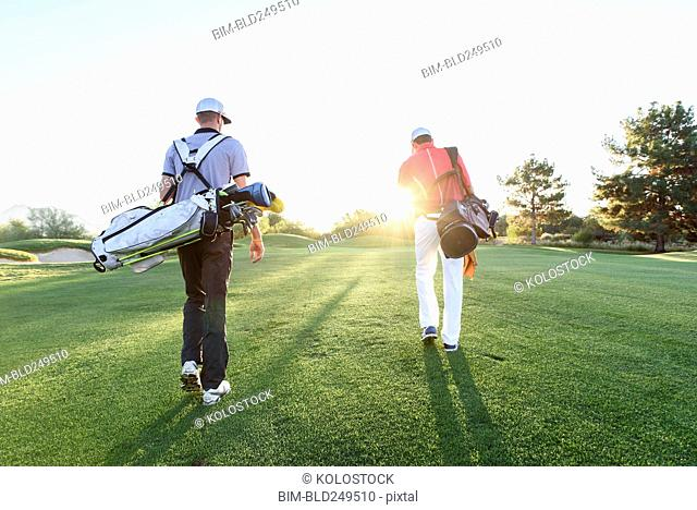 Men carrying golf bags on sunny golf course