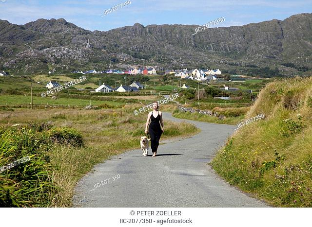 A woman walks down a quiet road with her dog near allihies, county cork ireland