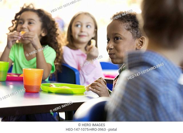 Children eating snacks in elementary school classroom