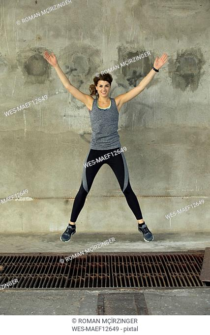 Young woman during workout, jumping jack